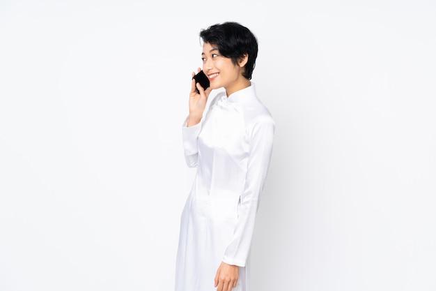 Молодая вьетнамская женщина с короткими волосами в традиционном платье на белой стене ведет с кем-то разговор по мобильному телефону Premium Фотографии