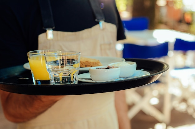 Young waiter holding tray. Premium Photo