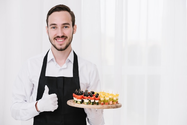 Young waiter showing appetizers Free Photo