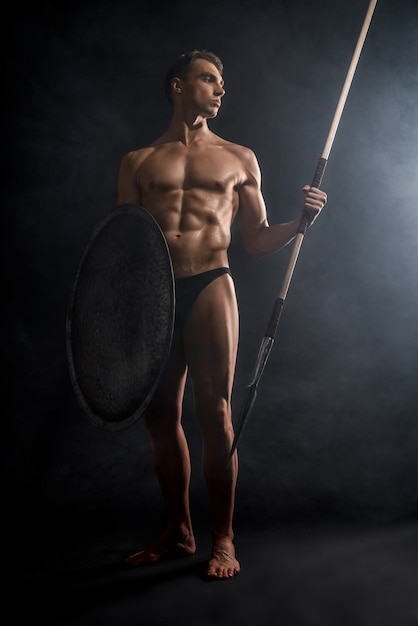 Young warrior holding spear and shield. Free Photo