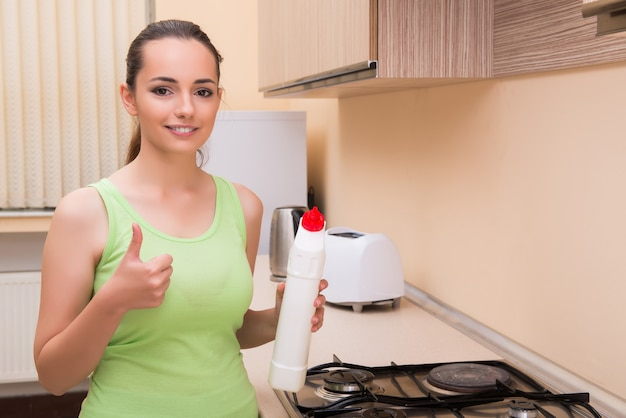 Young wife cleaning kitchen holding bottle Premium Photo