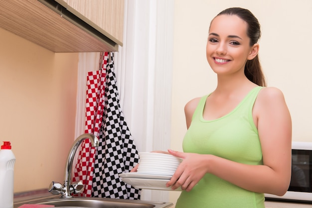 Young wife woman washing dishes in kitchen Premium Photo