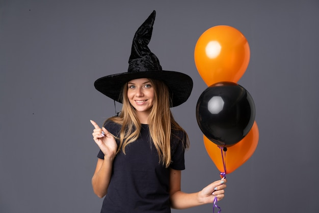 Young witch holding black and orange air balloons pointing finger to the side Premium Photo