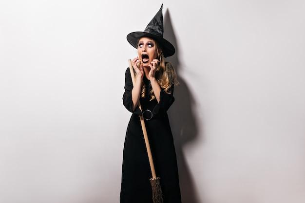 Молодая ведьма в шляпе позирует на хэллоуин со страшным выражением лица. фотография в помещении потрясенной блондинки-модели в костюме волшебника. Бесплатные Фотографии