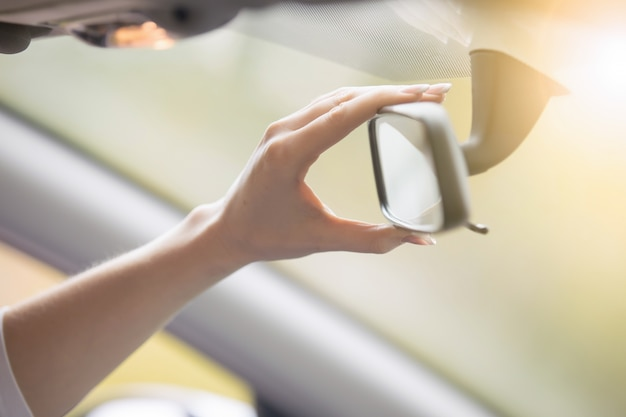 Young woman adjusting a rear-view mirror in the car Free Photo