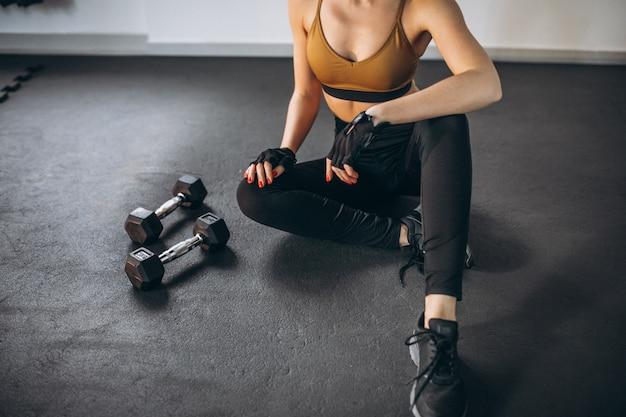 ダンベルでジムで運動する若い女性 無料写真