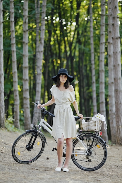 Young woman against nature background with bike Free Photo