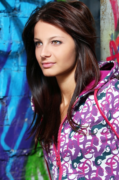Young woman against wall with graffiti Free Photo