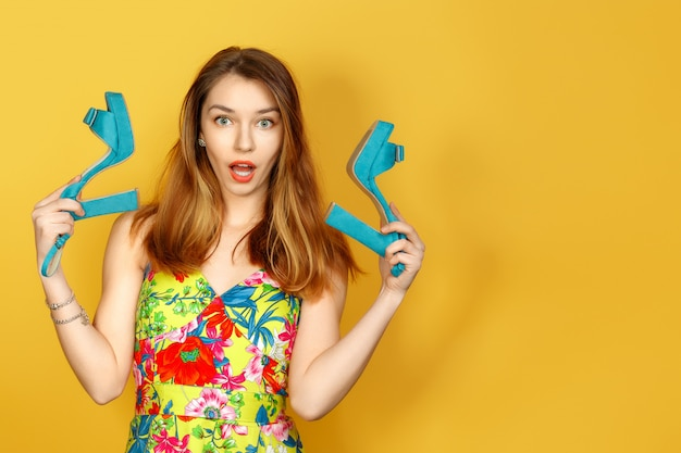 Young woman against yellow wall with flowers in hand Premium Photo
