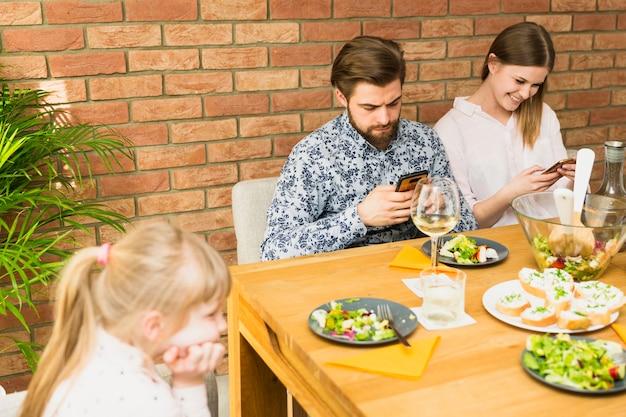 テーブルに座っている若い女性とハンサムな男 無料写真