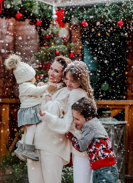 Молодая женщина и ее дети в зимних свитерах, позирующих на заднем дворе с рождественским фоном. идет снег. Premium Фотографии
