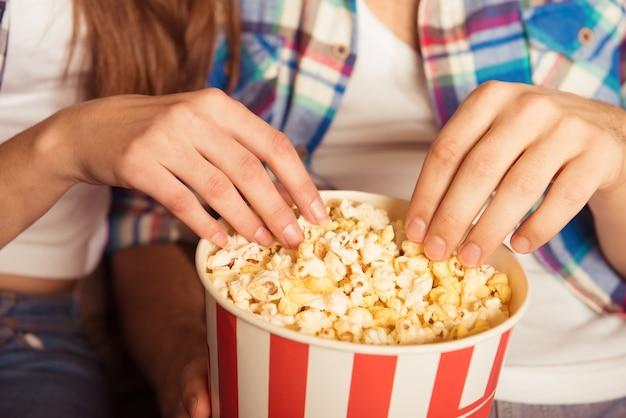 映画館でポップコーンを食べる若い女性と男性 Premium写真