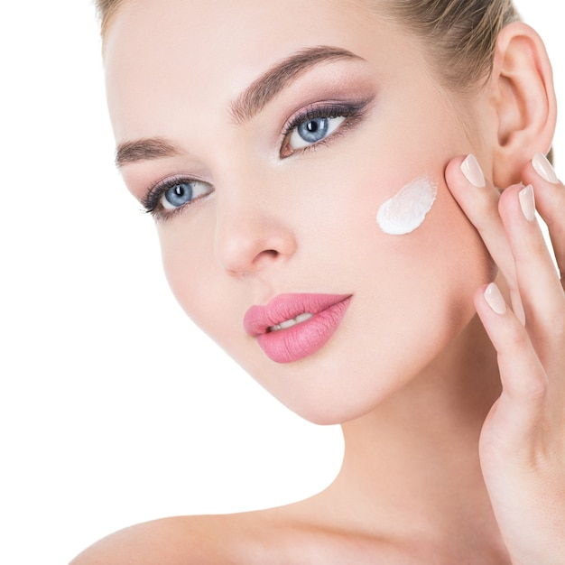 Young woman applies cosmetic cream on a face. Free Photo