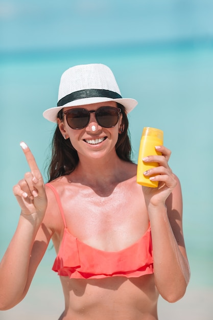 Young woman apply cream on her nose at beach Premium Photo