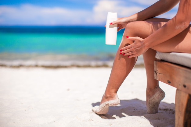 Young woman apply cream on her smooth tanned legs at tropical beac Premium Photo