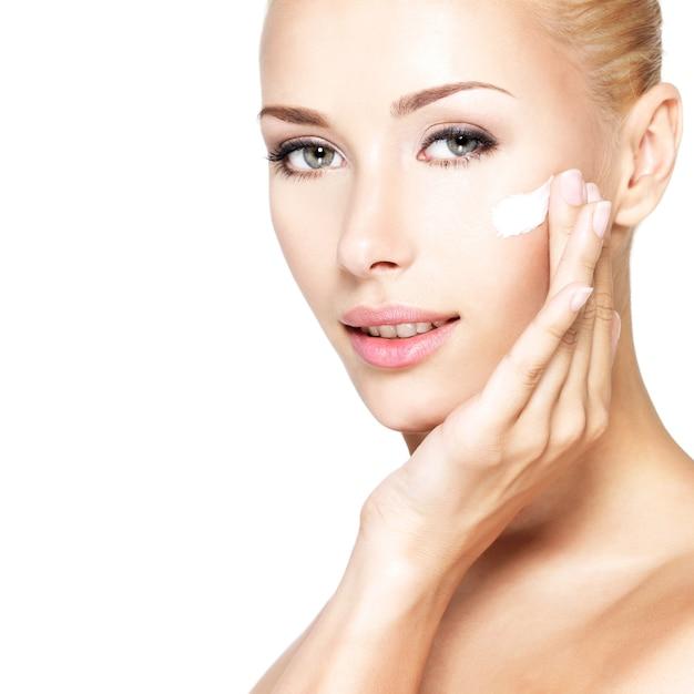 깨끗하고 신선한 얼굴에 화장품 크림을 적용하는 젊은 여자 무료 사진