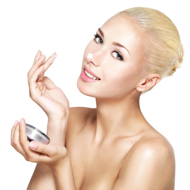 코-절연에 화장품 크림을 적용하는 젊은 여자 무료 사진