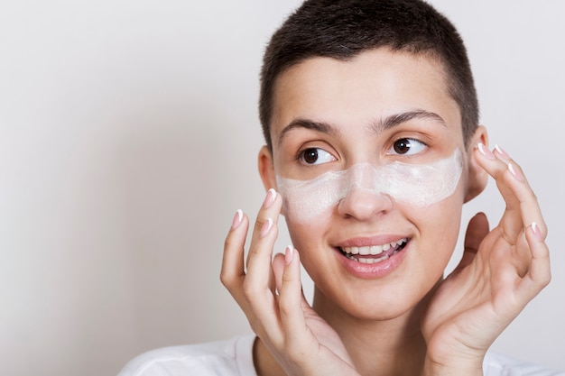 Young woman applying face cream Free Photo