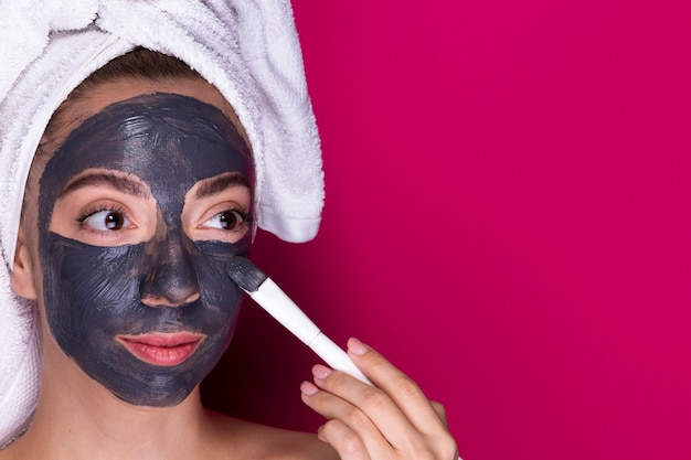 Young woman applying face mask Free Photo