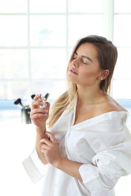 香水を適用する若い女性。 無料写真