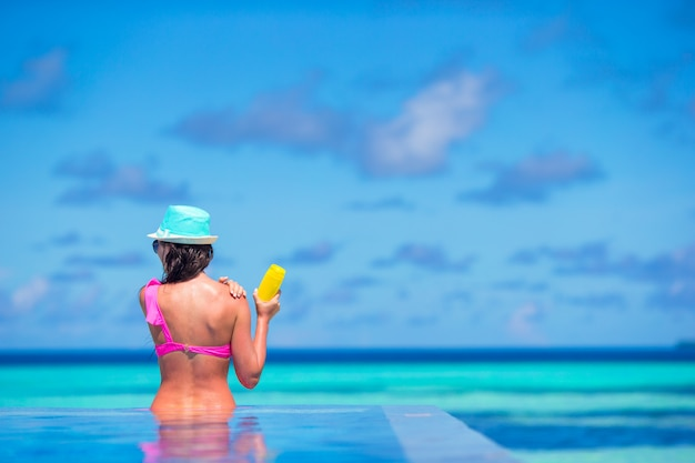 Young woman applying sun cream during beach vacation Premium Photo