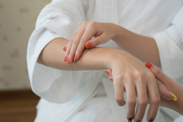Young woman applying with finger white moisturizing cream on hand. Free Photo