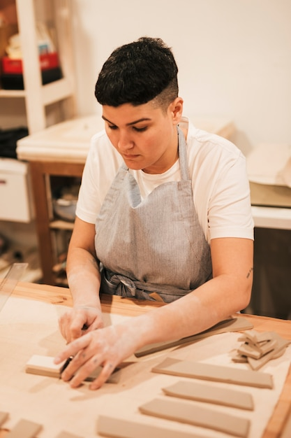 Young woman in apron cutting the clay with tools on wooden table Free Photo