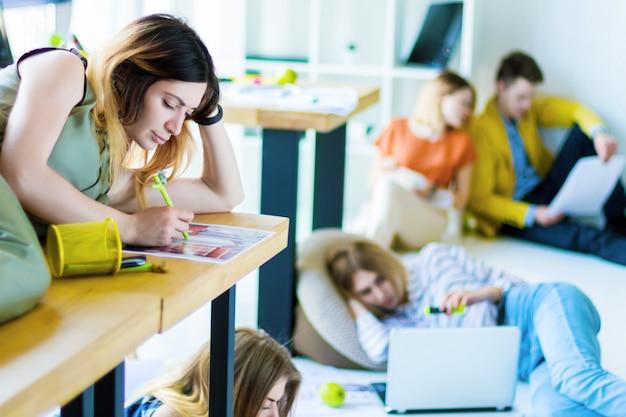 若い女性の建築家、軽いオフィスのデスクトップに横たわって働くインテリアデザイナー。背景に、創造的な労働者は、床に座って非公式の会合でデザインプロジェクトについて考えています。 Premium写真