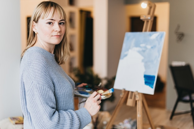 Young Woman Artist Painting A Picture In Studio Photo