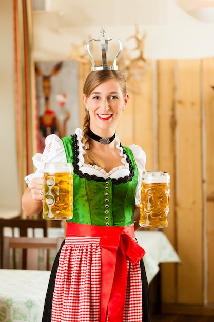 Young woman as queen in traditional bavarian tracht in restaurant Premium Photo