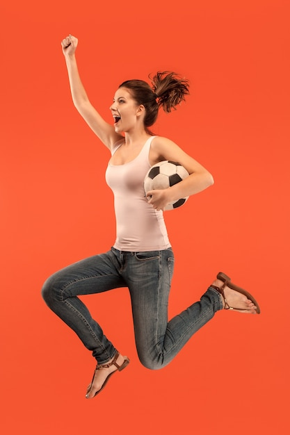 The young woman as soccer football player jumping and kicking the ball at studio on a red background. Free Photo