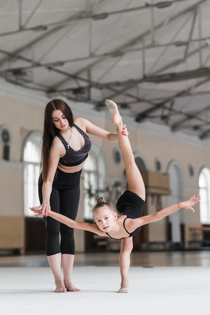 Young woman assisting ballerina girl in dance class Free Photo