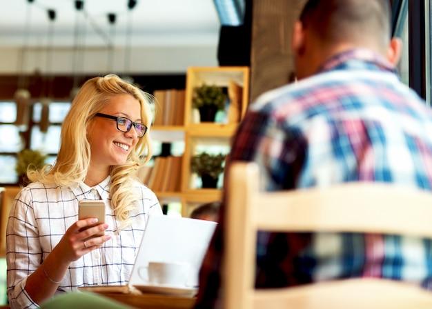 Молодая женщина в кафе-баре, набрав сообщение на мобильный телефон. Premium Фотографии