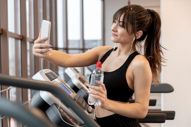 Молодая женщина в тренажерном зале, принимая selfies Бесплатные Фотографии