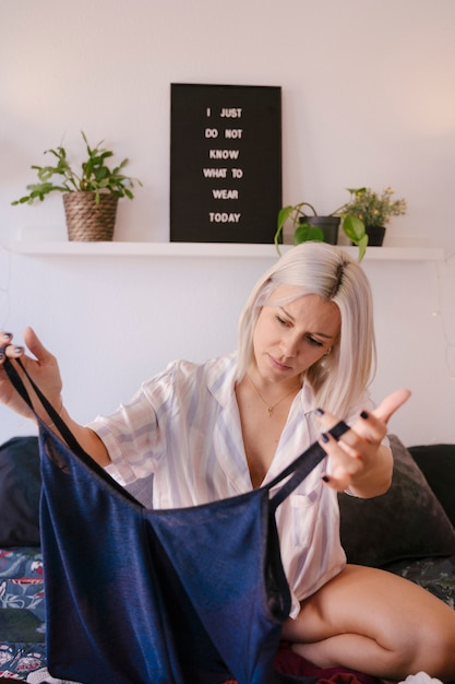 Молодая женщина дома выбирая ее модный наряд Premium Фотографии