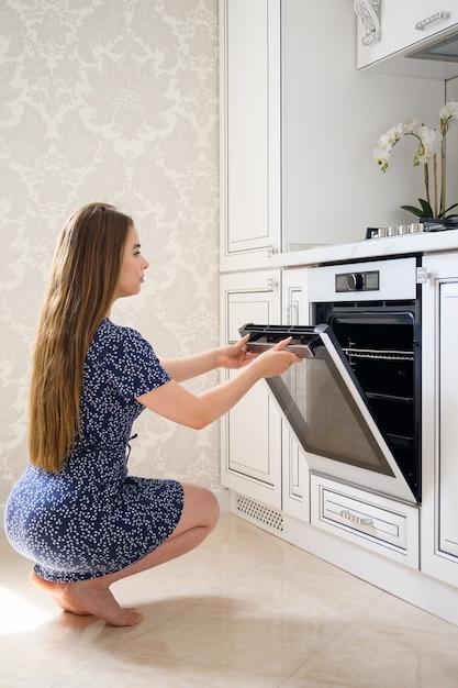 豪華でモダンな古典的な白いキッチンのインテリアで若い女性 Premium写真