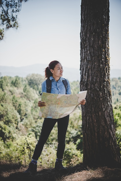 Young woman backpacker hiker reading map hiking trip. relaxing on holiday. Free Photo