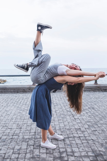 Young woman balancing friend on her back standing near the sea Free Photo