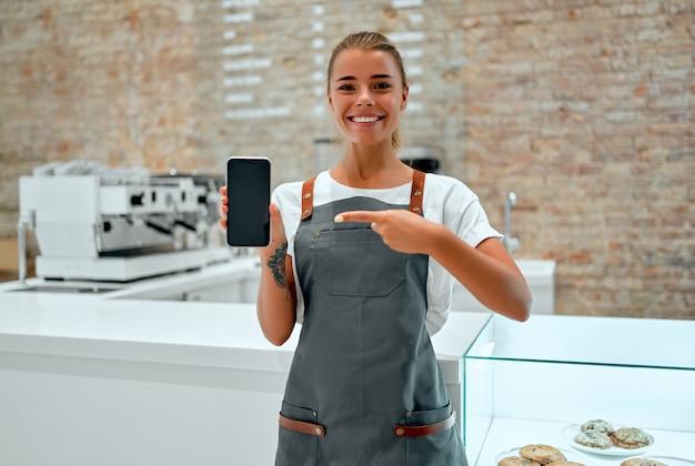 若い女性のバリスタは、コーヒーショップのカウンターに立って、空白のスマートフォンの画面を表示しながら微笑んでいます。 Premium写真