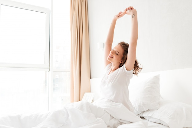 Young woman in bed indoors stretching Free Photo
