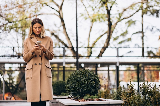 Young woman in beige coat using phone outside the street Free Photo