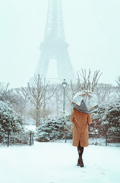 Young woman in a beige coat walks under an umbrella in a snowy winter paris Premium Photo