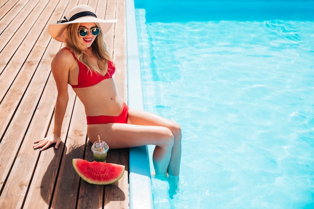 Young woman being happy at the edge of the pool Free Photo