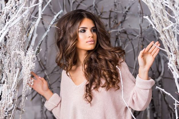 Young woman in big pink knitted sweater posing in decorated studio winter forest Free Photo