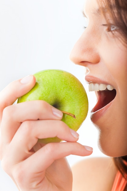 Young woman bites in a fresh and healthy apple Premium Photo