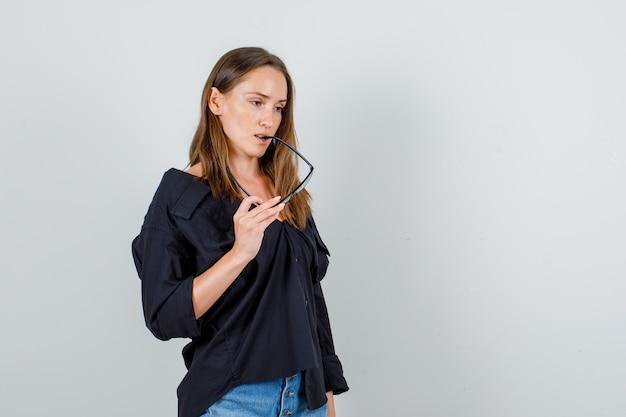 シャツ、ショートパンツの正面図を考えながら眼鏡をかむ若い女性。 無料写真
