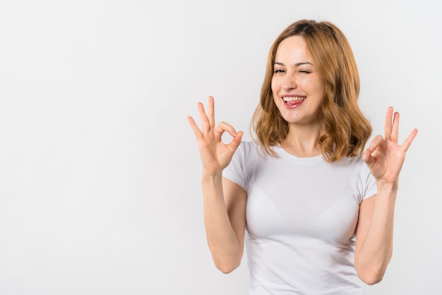 Young woman biting her tongue showing ok gesture with two hands winking Free Photo