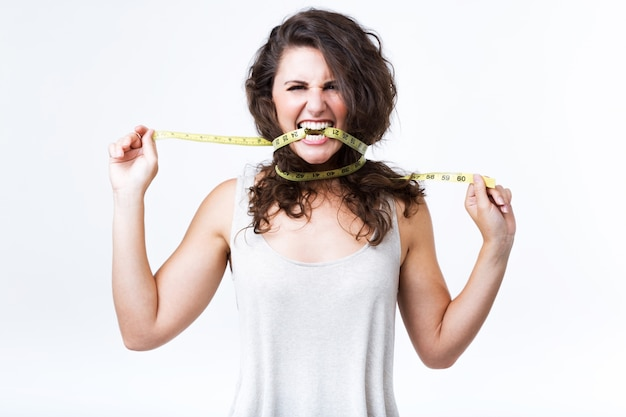 Young woman biting tape measure over white background. Free Photo