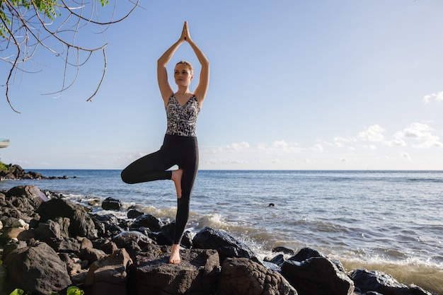 Young woman in black doing yoga on rock beach Premium Photo