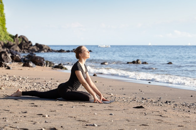 Young woman in black doing yoga on sand beach Premium Photo